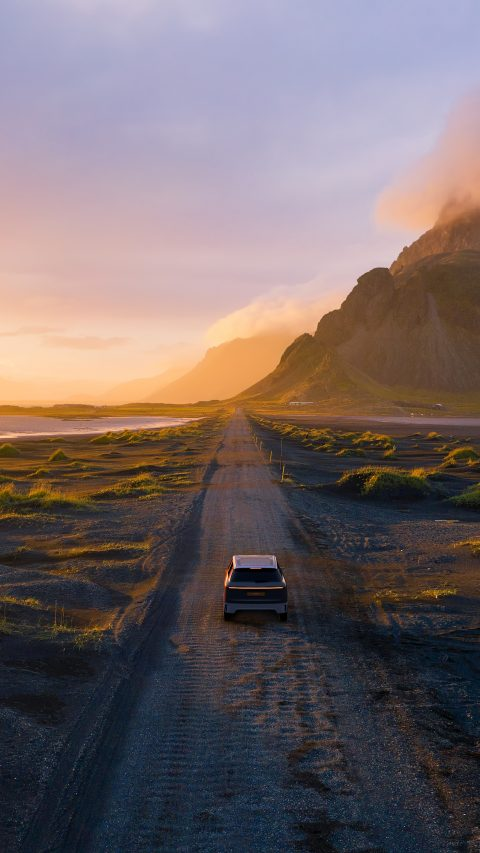 Gravel road at a golden Sunset with Vestrahorn mountain in the background and a car driving the road in Iceland